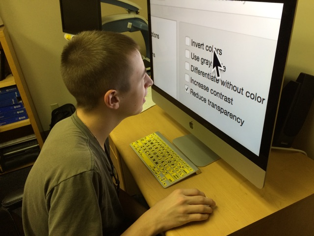 A student selects background options for a computer screen on a Mac under System Preferences.