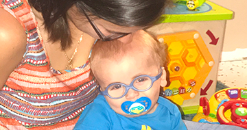 A woman kissing the top of the head of a baby wearing glasses