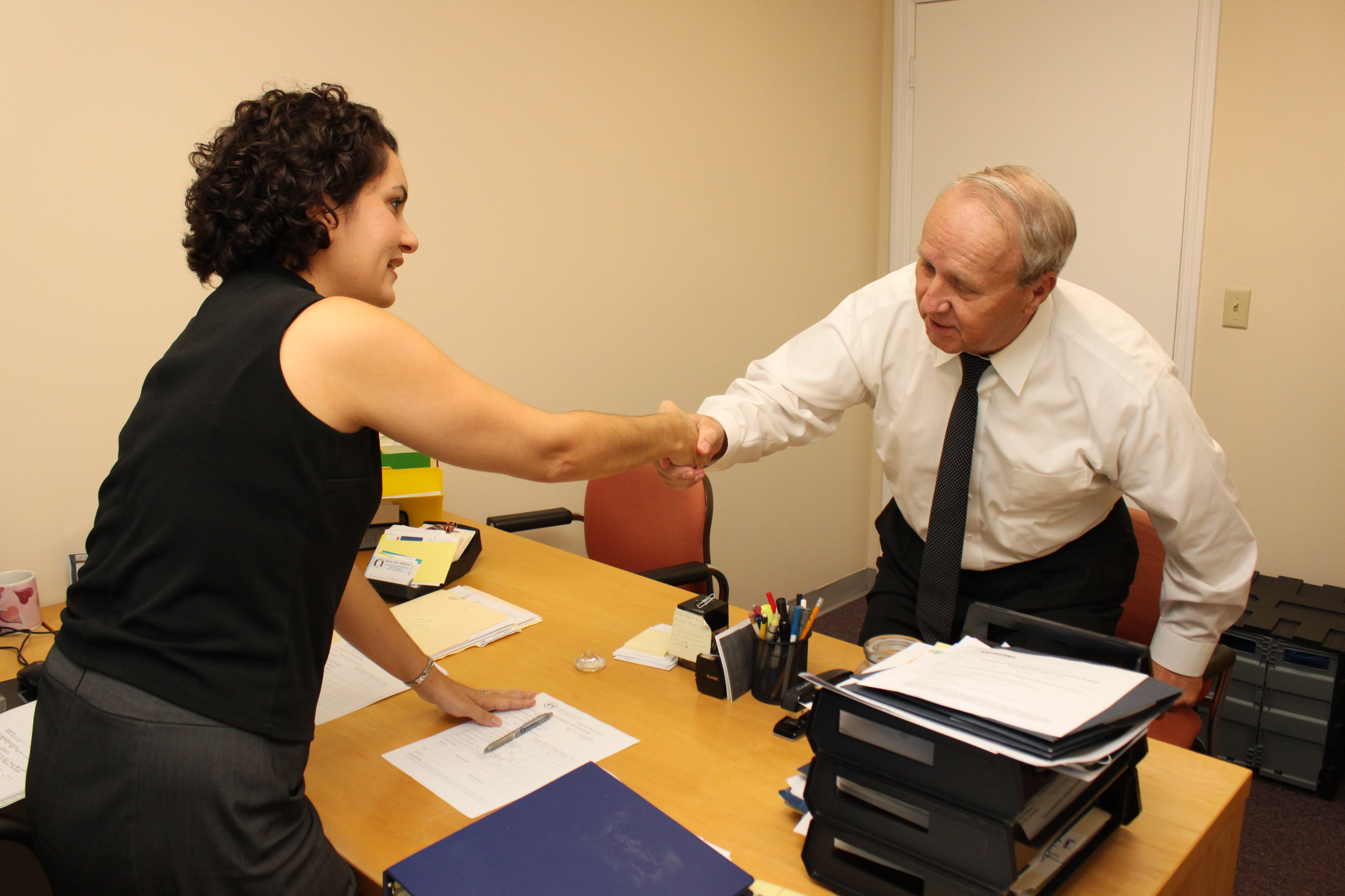 Rosemary Mulero shaking hands with a participant who is sitting across a desk.