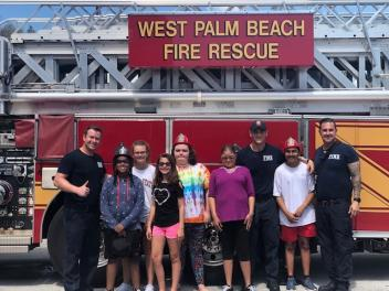 Transition students visit with the West Palm Beach Fire Fighters and they pose in front of a fire truck.