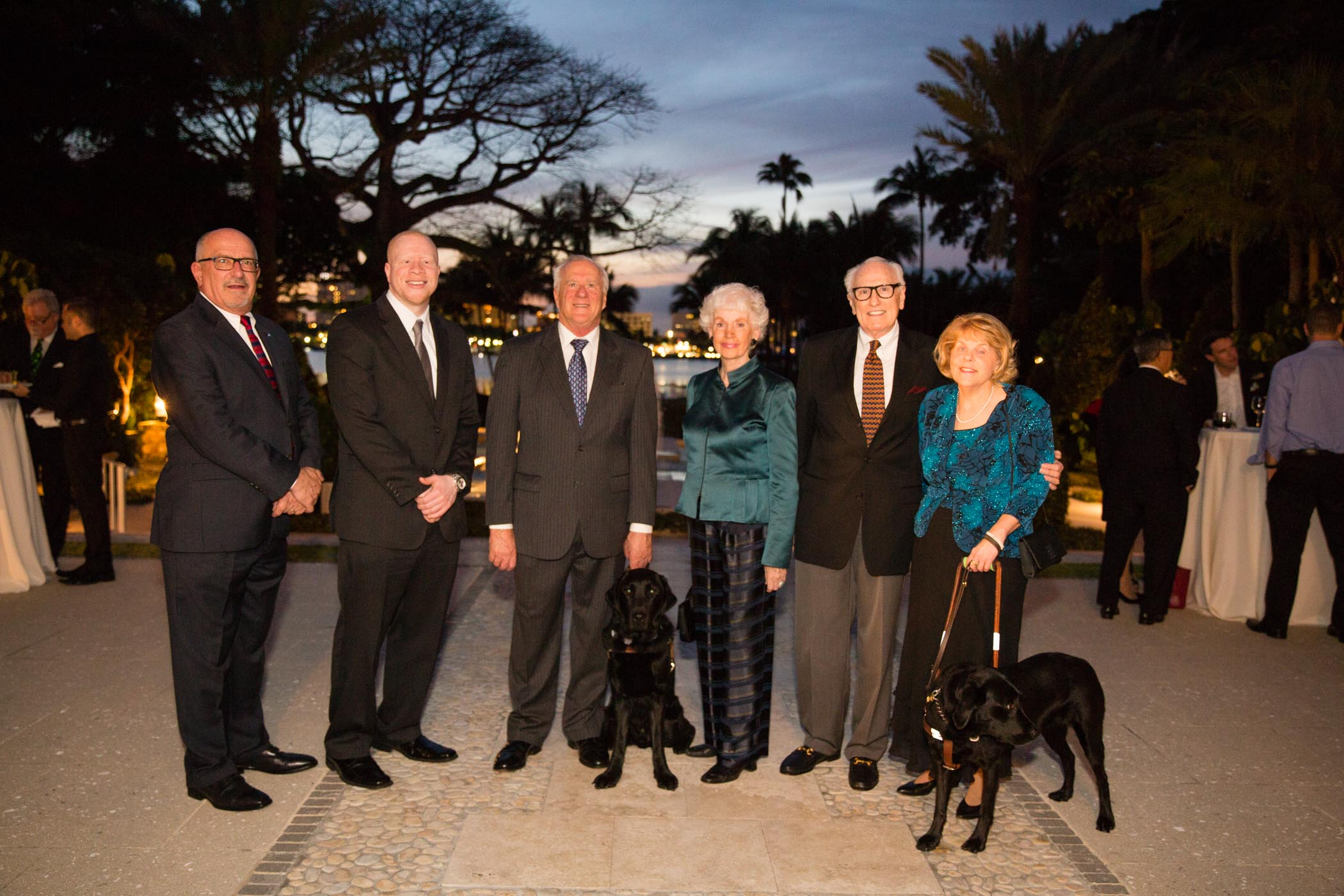 Several Lighthouse board members pose for a picture at an evening event with two dog guides.