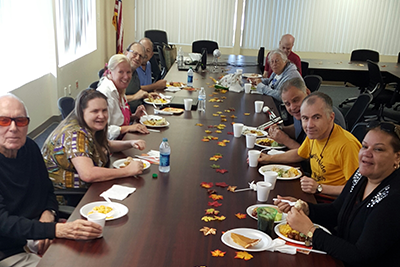 Ten men and women sit at a long table strewn with fall leaves as they eat.