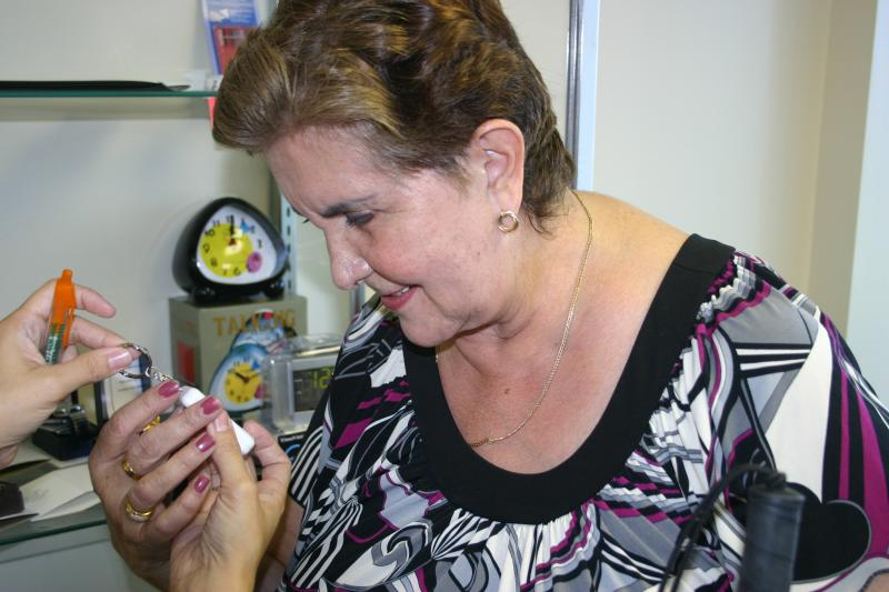 A woman is exploring a talking keychain at the Aids and Appliances store.