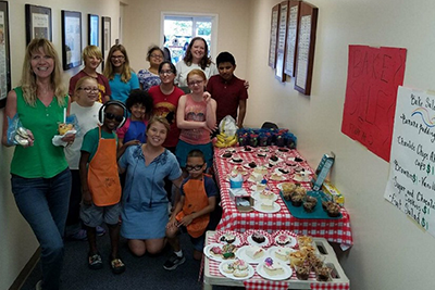 Ten children stand by their bake sale table with three instructors smiling big as they stand next to tables filled with baked goods.