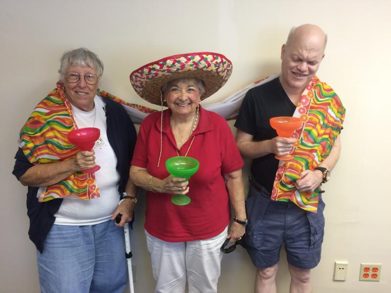 Three participants celebrating Cinco de Mayo at the Lighthouse Focus Group, wearing ponchos and sombreros.